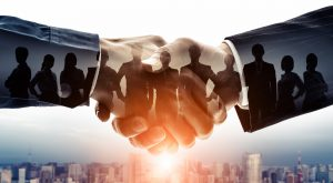 Two hands shake while an image of a team of business people is super imposed within.