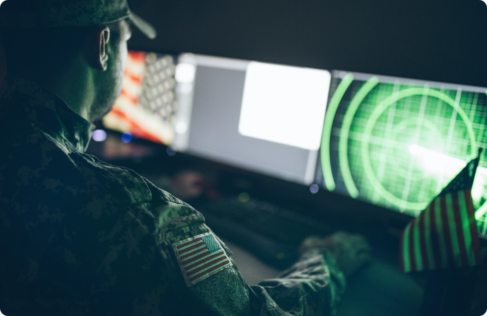 A soldier looks over various monitors while working.